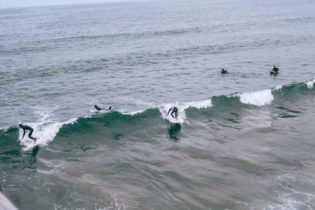 unrecognizable sportsmen practicing surfing on ocean waves