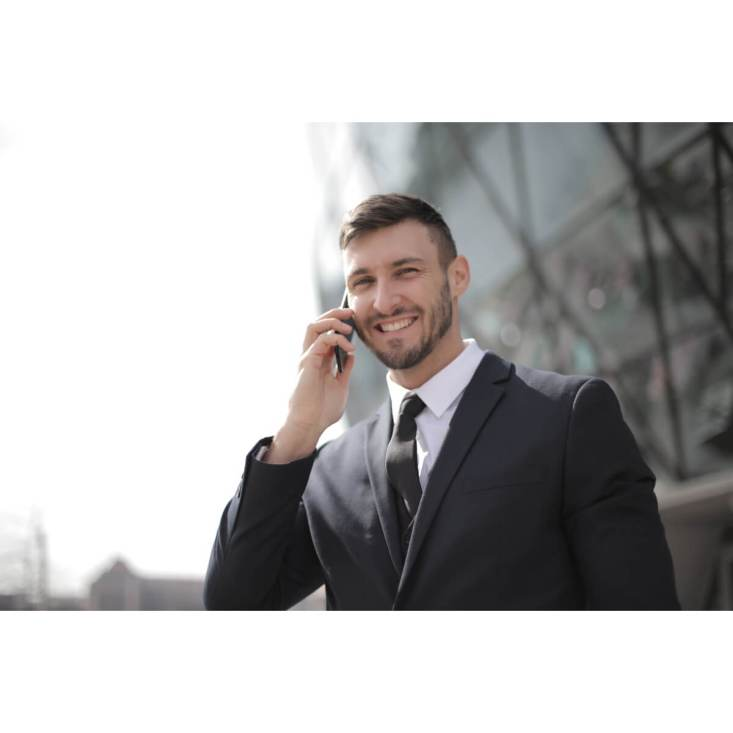 How to develop better self-esteem |  A Young businessman is smiling on the street when talking to someone on the phone