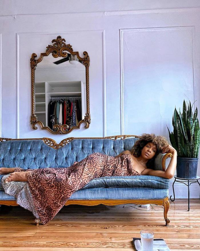 Influencer Karen Britchick lying across a blue velvet chez lounge in her sitting room wearing a leopard print slip dress. There's a mirror and a big potted plant in the background, and a glass of water on the floor in front of her.