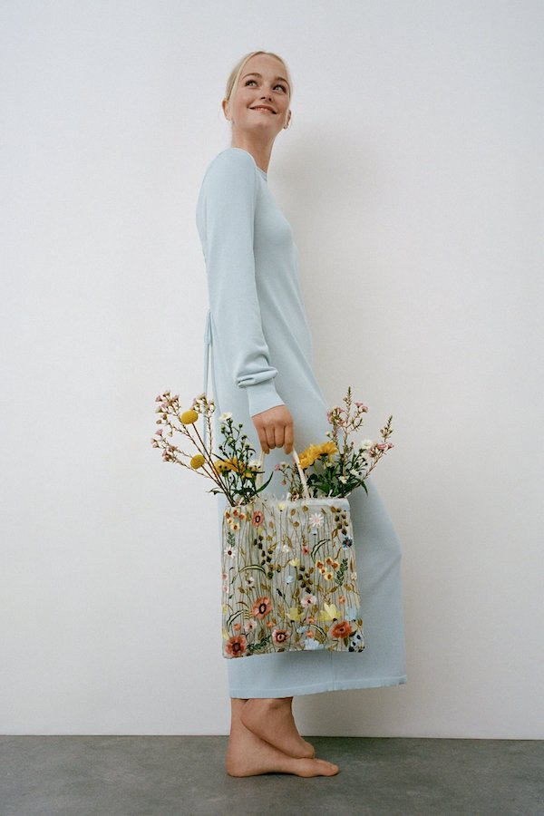 White woman with tied back blonde hair wears a knitted blue long-sleeve maxi dress and Zara floral bag with flowers inside.