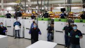 Stirling Ultracold employees stand with the company's freezers.