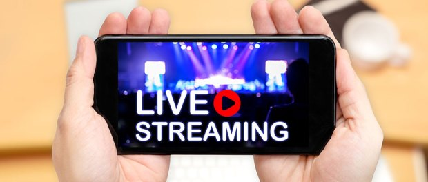 Looking down to see two hand holding mobile phone with Live Streaming word on screen and blur desk office background,Video marketing concept