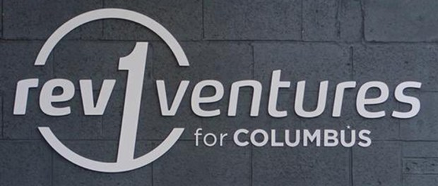 REV1Ventures-Logo-on-a-gray-brick-wall