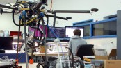 A technician works on a computer with a drone nearby