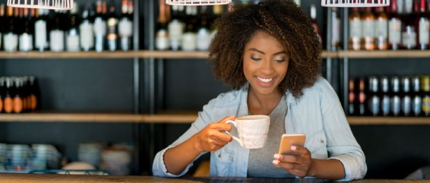 Happy black woman on her cell phone looking for places to visit while having a cup of coffee at a cafe