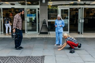 A man and two women. One woman is crouched with her hands on the floor.