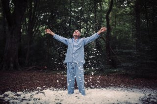 Man in pyjamas standing in the woods throws feathers in the air