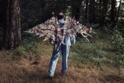 A man wearing wings made from various fabrics.