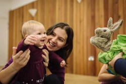 A mum and baby smiling at two hand puppets.