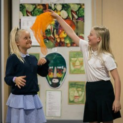 Two girls. One is throwing an orange piece of fabric.