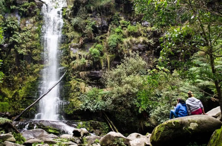 8 Ridiculously Beautiful Victorian Waterfalls To Chase This Summer Pat Corden Erskine Falls, waterfall, bush, person, rocks