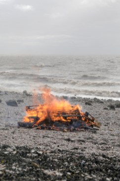 The bonfire burns as the tide returns