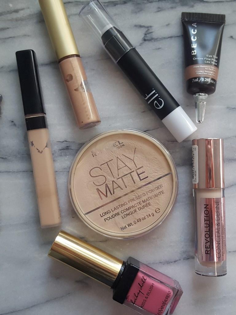 Overlay of summer makeup products; Rimmel Stay Matte Powder; Maybelline Fit Me Concealer; Revolution Conceal & Define Concealer; YSL Baby Doll Kiss & Blush; Becca Shimmering Skin Perfector; Elf Highlighting Stick; Becca Eye Tint