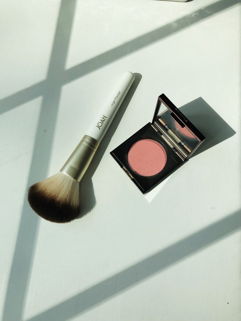 Flesh Tender Flesh Blush in Pulse, posed with the Large Powder Brush from Joah Beauty