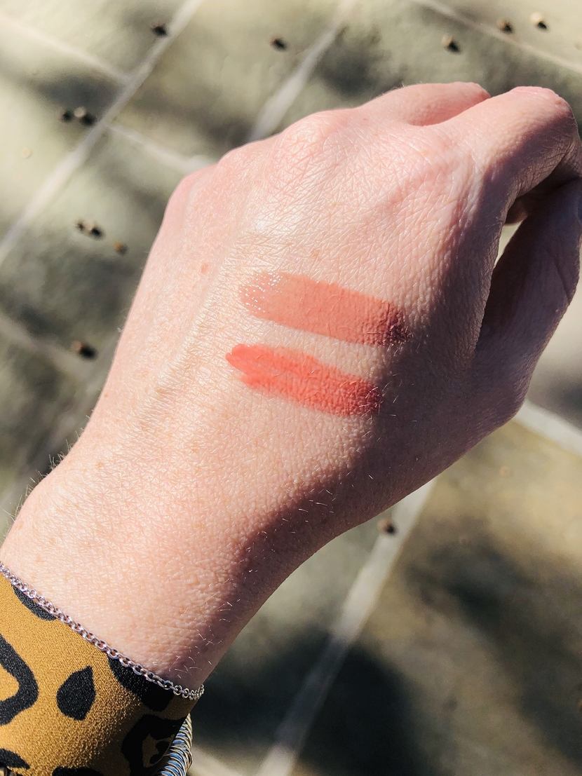 Drugstore vs. luxury lip gloss battle! Swatches of Hourglass Unreal High Shine Volumizing Lip Gloss in Sublime (top), and Revlon Kiss Plumping Lip Creme in Apricot Silk (bottom).