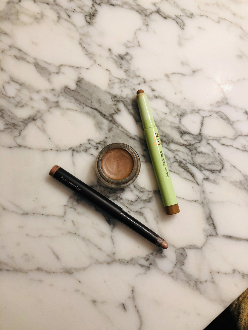 Flatlay with my fave no-eyeshadow eyeshadows including Laura Mercier Caviar Stick in Au Naturel, MAC Paint Pot in Grounwork, & Pixi Endless Shade Stick in Matte Cognac