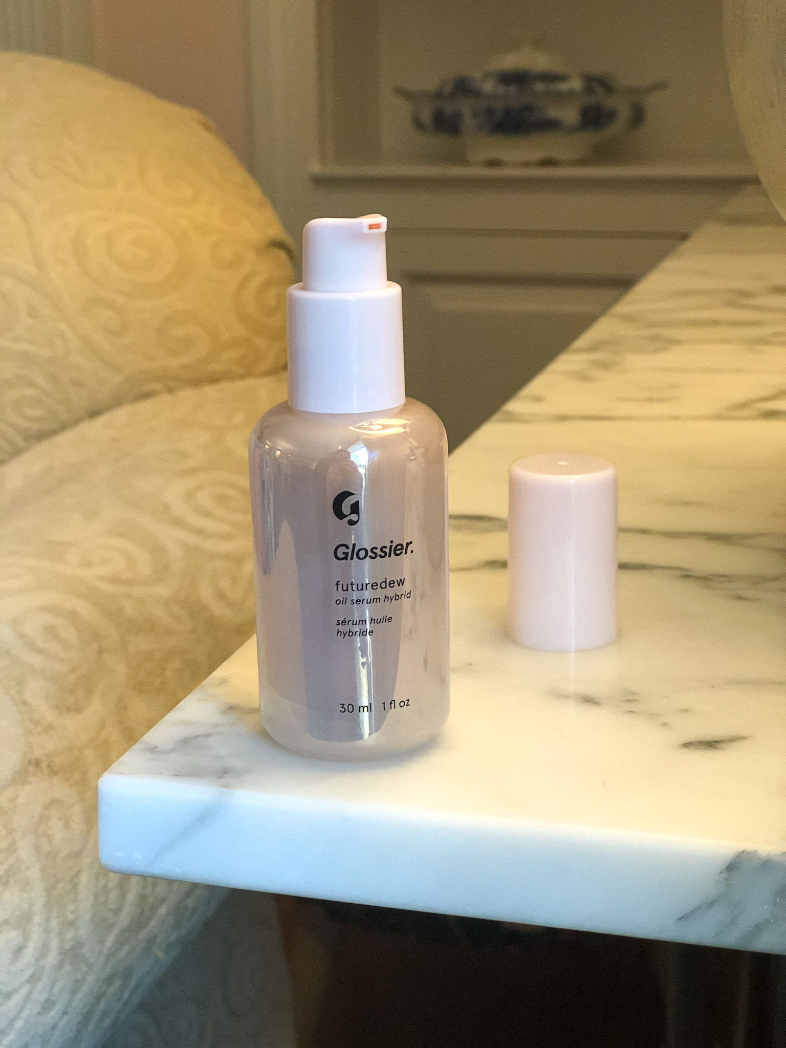 Glossier Futuredew, posed on a marble table