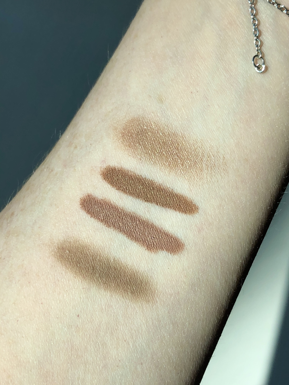 swatches of my everyday eyeshadows: from top to bottom, MAC Paint Pot in Groundwork, Bobbi Brown Cream Shadow Stick in Taupe, Bobbi Brown Cream Shadow in Nude Beach, and Maybelline Color Strike Eye Shadow Pen in Flare
