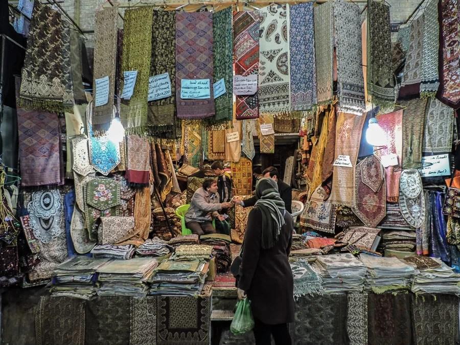Una ragazza velata osserva la merce nel bazar di Shiraz