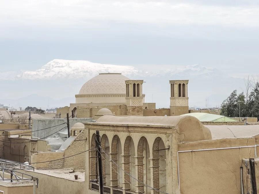 Le torri del vento di Yazd e le montagne innevate all'orizzonte viste da uno dei suoi tetti