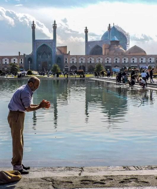 Davanti alla moschea dello Scià un uomo di rinfresca con l'acqua della fontana della piazza