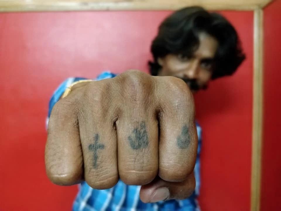 Kumar fa vedere le sue nocche: Le tre maggiori religioni dell'India impresse sulle nocche, perché la sola cosa che conta è il cuore e che questo sia musulmano, indù o cristiano in questo gruppo di amici conta... zero.