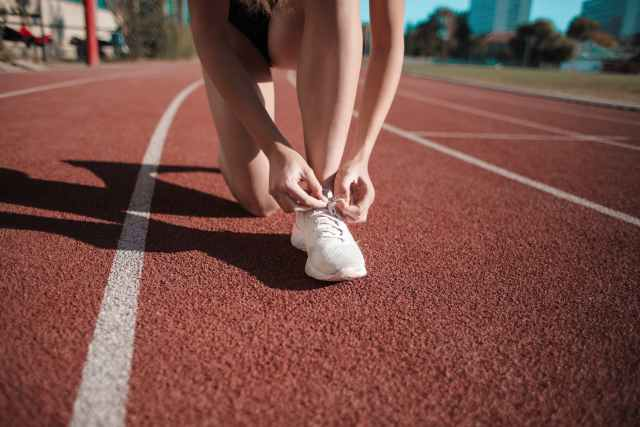 close up photo of woman tying her white sneakers on running track