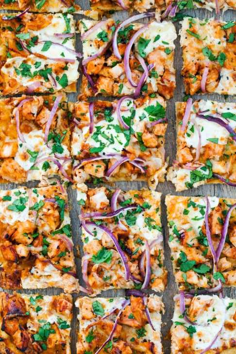 Bird's eye view of BBQ chicken pizza cut into squares with cheese, chicken, BBQ sauce, red onion, and cilantro as toppings