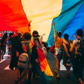 An image of young people at a pride march with an LGBT flag