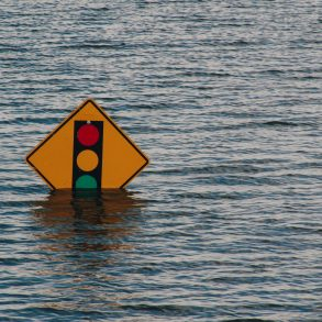 A traffic light half submerged in water