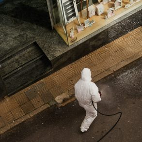 A man in Hazmat suit disinfecting the pavement