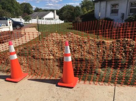 Safety fence around temporary hole exposing the sanitary line.