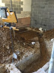 Digging to place plumbing pipes in new ladies' room.