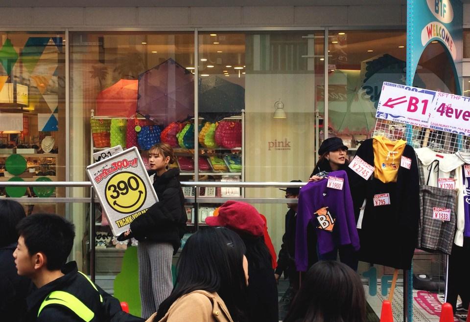 Twee Japanse verkoopmedewerksters met reclameborden