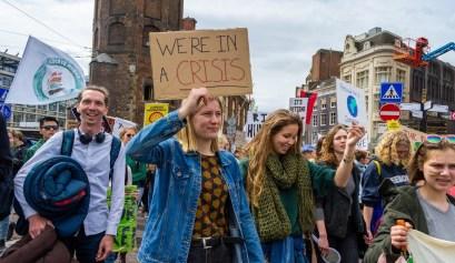 een klimaatactivist houdt een bord omhoog met de tekst we´re in a crisis´
