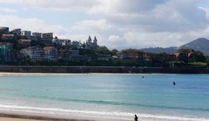 Een man loopt over het strand van San Sebatian met op de achtergrond de zee en de stad