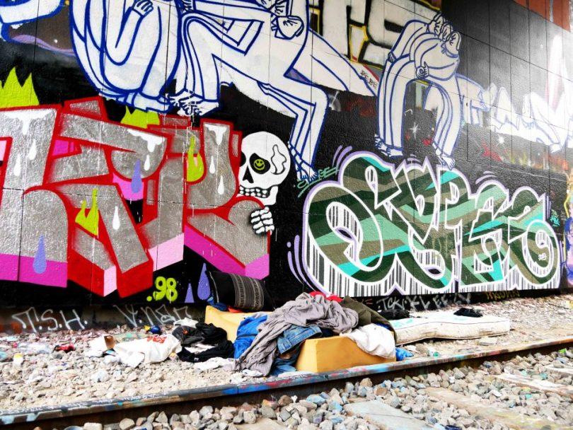 Een matras op de grond voor een muur vol graffiti