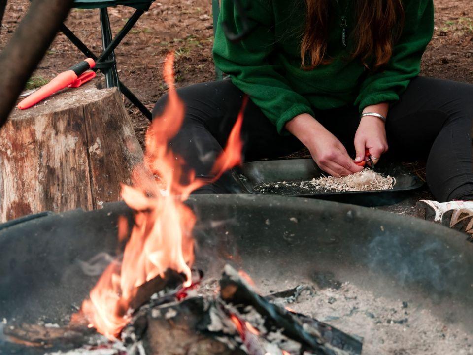 Laura in de weer met een firesteel. Op de voorgrond brand het kampvuur al.