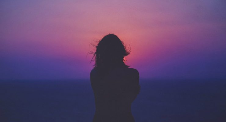 The black silhouette of a woman looking towards the sky as she stands in front of a vivid pink and purple sky.