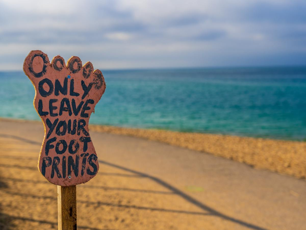 A sign in the shape of a foot saying 'only leave your foot prints'