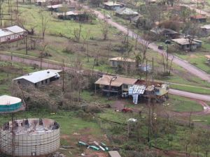 Bare trees and damaged houses and land from a tropical cyclone