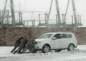 people pushing a vehicle during a blizzard