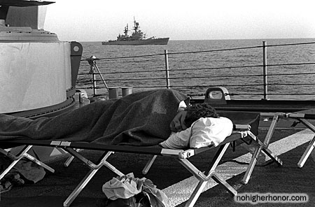 Fireman James Seward sleeps on the forecastle of the guided missile frigate SAMUEL B. ROBERTS (FFG-58). Some of the crew are sleeping on the deck because of hull damage sustained when the ship struck a mine on April 14, 1988. The guided missile cruiser USS JOUETT (CG-29) is in the background.