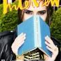 Victoria Beckham en la portada de Interview Magazine, vistiendo chaqueta de cuero negro, blusa a rayas y sosteniendo un libro en sus manos.