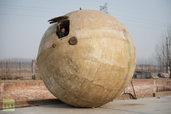 Farmer Liu Qiyuan posing with survival pods that he created and dubbed ′Noah′s Arc′, in the village of Qiantun, Hebei province, south of Beijing (AFP Photo / Ed Jones)
