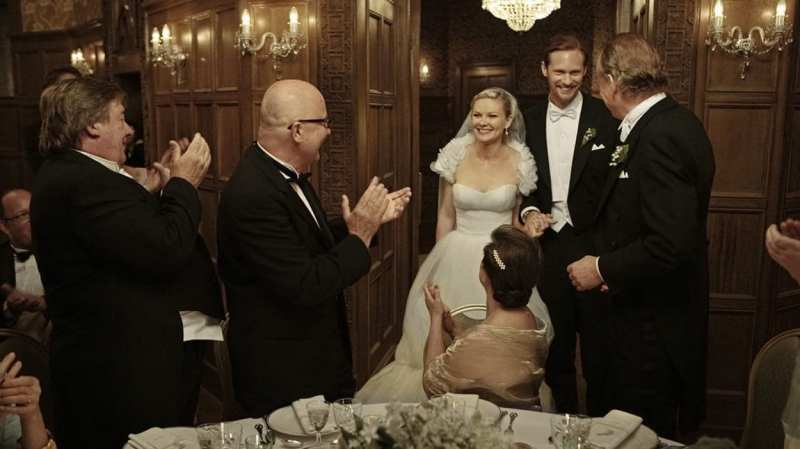 Justine and Michael enter a room of people clapping after getting married