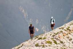 persone_camminano_su_cresta_montagna_vettore_da_raw