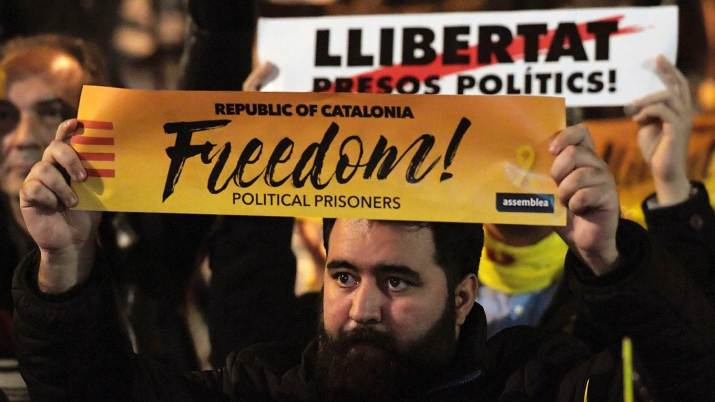 Protesters hold banners reading 'Freedom for political prisoners'
