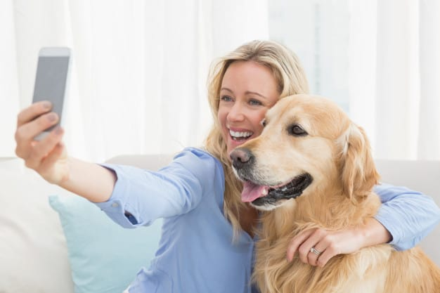 Mulher abraçando o cachorro para tirar uma foto