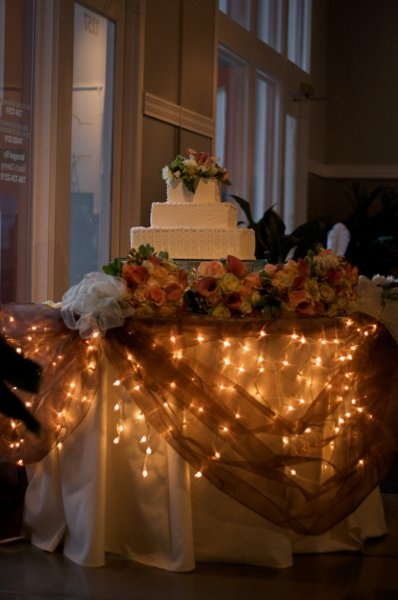 I like the idea of the cake, food, gift and sweetheart table being lighted underneath with ivory table clo